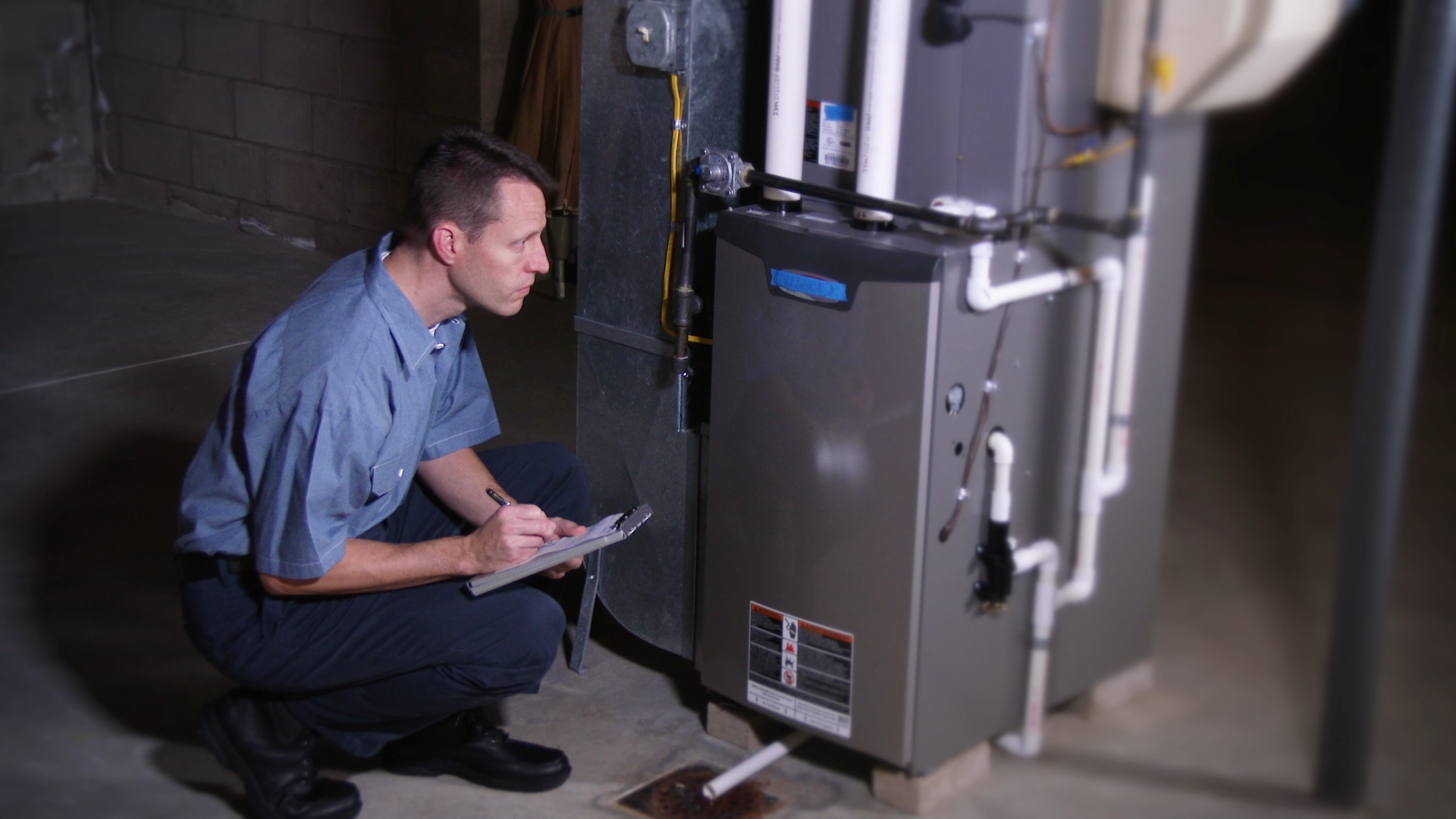 Service man looking at heater for winter furnace tune up